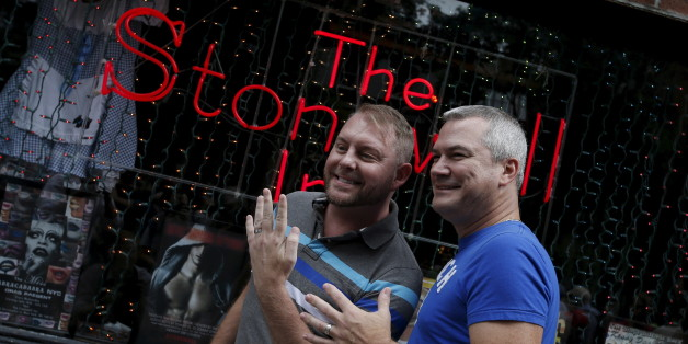 Charles Wooton (R) and Keith Newport, both from Atlanta, Georgia, show their wedding rings outside the Stonewall Inn in the Greenwich Village neighborhood of New York, June 26, 2015, following the announcement that the U.S. Supreme Court had ruled that the U.S. Constitution provides same-sex couples the right to marry in a historic triumph for the American gay rights movement.  REUTERS/Mike Segar