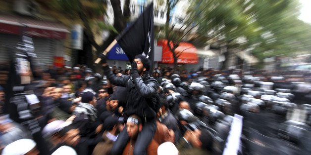 FILE - Tunisian Salafists confront police officers during a demonstration in Tunis, in this Friday, Feb. 17, 2012 file photo. The cradle of the Arab Spring, Tunisia also has a long history of frustrated youth heading off to fight in foreign jihads. Now, according to figures released by the Syrian government, they may make up a large percentage of Arabs who have gone to join the struggle against the regime of Bashar Assad. And that has raised alarm both about radicalization in the Syrian rebel movement, and of rising extremism within newly-democratic Tunisia itself. (AP Photo/Amine Landoulsi, File)
