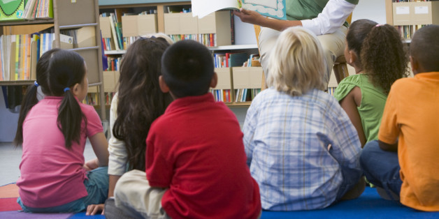 Kindergarten teacher reading to children in librar