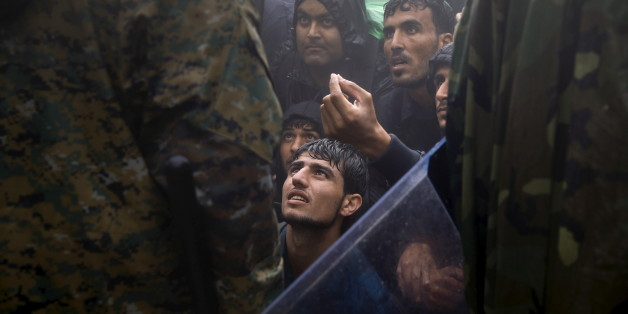 Migrants and refugees beg Macedonian policemen to allow passage to cross the border from Greece into Macedonia during a rainstorm, near the Greek village of Idomeni, September 10, 2015. Reuters and The New York Times shared the Pulitzer Prize for breaking news photography for images of the migrant crisis in Europe and the Middle East. REUTERS/Yannis Behrakis      TPX IMAGES OF THE DAY