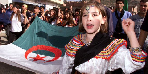 A young girl from the Kabylie region wears a traditional costume as sheholds the Algerian flag during a march in Ighil Imoula, some 100 kmseast of the country's capital of Algiers, November 1, 2001. Severalthousand people from the restive Berber-speaking Kabylie region,traditionally a region of opposition to central rule, march to maintainpressure on the Algerian government about deep-rooted grievances.REUTERS/Zohra BensemraZB/JES/