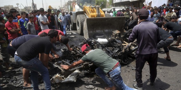 Civilians help a municipality bulldozer cleans up while citizens inspect the scene after a car bomb explosion at a crowded outdoor market in the Iraqi capital's eastern district of Sadr City, Iraq, Wednesday, May 11, 2016. An explosives-laden car bomb ripped through a commercial area in a predominantly Shiite neighborhood of Baghdad on Wednesday, killing and wounding dozens of civilians, a police official said. (AP Photo/ Khalid Mohammed)