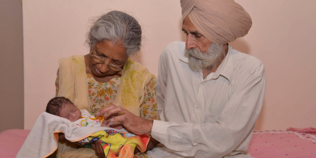 Indian father Mohinder Singh Gill, 79, and his wife Daljinder Kaur, 70, pose for a photograph as they hold their newborn baby boy Arman at their home in Amritsar on May 11, 2016.