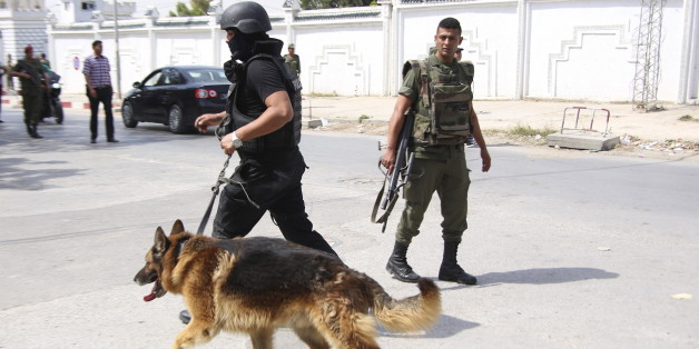 A Tunisian anti-terrorism brigade officer leads his dog after a shooting at the Bouchoucha military base in Tunis, Tunisia May 25, 2015. A Tunisian soldier opened fire on colleagues at a military base in the capital Tunis on Monday, killing a colonel and wounding eight other soldiers before he was shot dead himself, an army spokesman and a security source said. REUTERS/Zoubeir Souissi