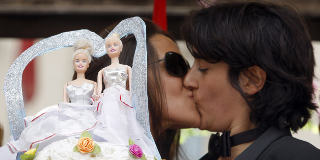 A lesbian couple kisses near a wedding cake as they take part in a gay pride parade in Rome June 7, 2008. Some 10,000 dancing and singing homosexuals and gay-rights supporters marched through Rome on Saturday, many of them chanting slogans against the Vatican and Italy's conservative new government.  REUTERS/Alessandro Bianchi        (ITALY)