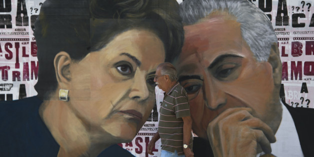 A man walks past a mural depicting Brazilian President Dilma Rousseff (L) and Vice-President Michel Temer at Paulista Avenue in Sao Paulo, Brazil on April 19, 2016. Brazil woke Monday to deep political crisis after lawmakers authorized impeachment proceedings against President Dilma Rousseff, sparking claims that democracy was under threat in Latin America's biggest country. / AFP / NELSON ALMEIDA        (Photo credit should read NELSON ALMEIDA/AFP/Getty Images)