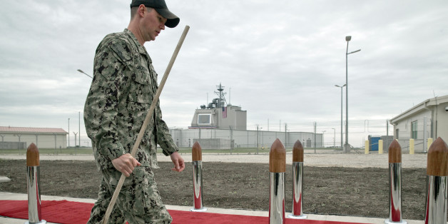 A US serviceman, backdropped by the radar building of a missile defense base, carries a mop in Deveselu, prior to an opening ceremony attended by U.S., NATO and Romanian officials at a base, originally established by the Soviet Union, in Deveselu, Southern Romania, Thursday, May 12, 2016. A U.S missile defense site in Romania aimed at protecting Europe from ballistic missile threats became operational Thursday, angering Russia which opposes having the advanced military system in its former area of influence.(AP Photo/Vadim Ghirda)