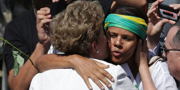 """A supporter hugs Brazilian President Dilma Rousseff as she leaves Planalto presidential palace in Brasilia, Brazil, Thursday, May 12, 2016.  Speaking hours after the Senate voted to suspend her on Thursday, Rousseff blasted the impeachment process against her as """"fraudulent"""" and promised to fight what she characterized as an injustice more painful than the torture she endured under a past military dictatorship. (AP Photo/Eraldo Peres)"""
