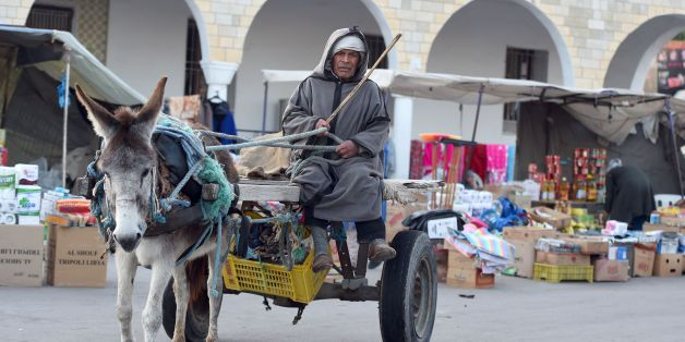 A Berber man dressed in traditional clothes rides a donkey-pulled-cart in the market of the town of Ben Guerdane, some 40 kilometres west of the Libyan border, on February 6, 2016.Tunisia on February 6, 2016 completed the construction of a barrier along its border with Libya, months after attacks on its national museum and a beach resort that killed dozens of tourists. Defence Minister Farhat Horchani told reporters that the construction of berms and water-filled trenches marks 'an important day