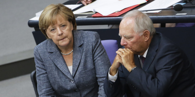 German Chancellor Angela Merkel, left, talks to Finance Minister Wolfgang Schaeuble during a debate at the German parliament prior to a vote on another bailout package for Greece, in the German Bundestag in Berlin, Wednesday, Aug. 19, 2015. (AP Photo/Markus Schreiber).