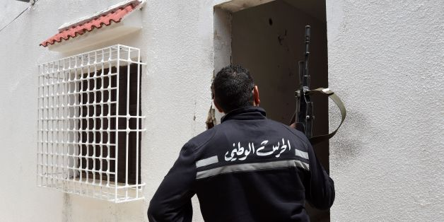 A Tunisian gendarme stands guard outside a house where two suspected jihadists were killed during a security operation on May 11, 2016 in the town of Mnihla, in Ariana province just outside Tunis. Sixteen others, some of them armed, were arrested during the operation, the interior ministry said in a statement. Since its 2011 revolution, Tunisia has faced a growing jihadist threat, with the Islamic State group last year claiming a string of deadly attacks on holidaymakers and security forces that