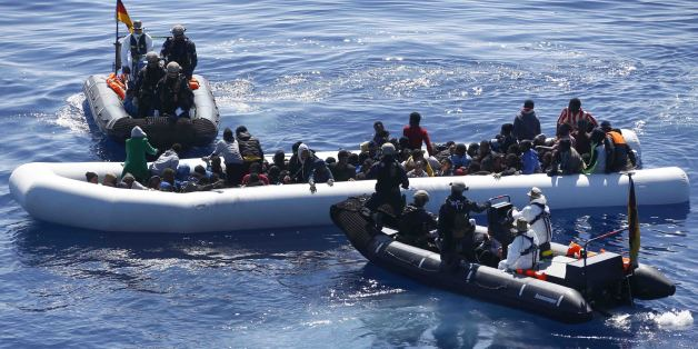 German Navy sailors surround a boat with more than 100 migrants near the German combat supply ship 'Frankfurt am Main' while operating in EUNAVFOR Med, also known as Operation Sophia, in the Mediterranean Sea off the coast of Libya Tuesday, March 29, 2016. (AP Photo/Matthias Schrader)