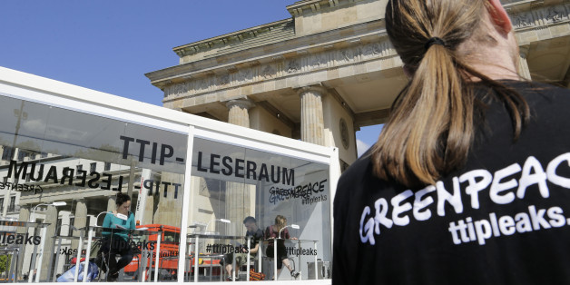 People read documents on the Trans-Atlantic talks to create a massive free trade zone between the United States and the European Union in a 'TTIP reading room' set up by Greenpeace in front of the Brandenburg Gate in Berlin, Germany, Monday, May 2, 2016. Greenpeace released confidential negotiating texts that the environmental group claims shows U.S. ill intent. (AP Photo/Ferdinand Ostrop)