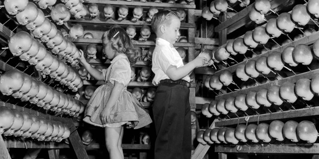 A young boy and girl inspecting dolls' heads at the Ideal Toy Company in Jamaica, Long Island, USA. The company is one of the largest toy manufacturers in the world.