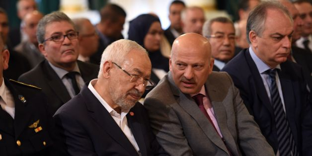 Tunisian Islamist Ennahdha party leader, Rached Ghannouchi (C-L), talks with Vice-President of Nidaa Tounes Ridha Belhaj (C-R) during a ceremony marking the 60th anniversary of Tunisia's independence at the Carthage palace in Tunis, on March 20, 2016, as the country reels from a series of deadly jihadist attacks that have battered its already struggling economy. 