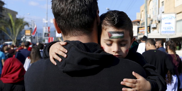An Israeli Arab boy sleeps as his father carries him during a Land Day rally in the northern Israeli village of Arrabe, March 30, 2016. Land Day commemorates the killing of six Arab citizens of Israel by security forces during protests in 1976 over government land confiscations. REUTERS/Ammar Awad      TPX IMAGES OF THE DAY