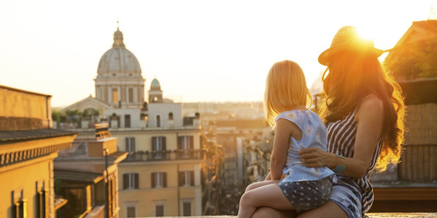 Mother and baby girl sitting on street overlooking rooftops of rome on sunset looking into distance
