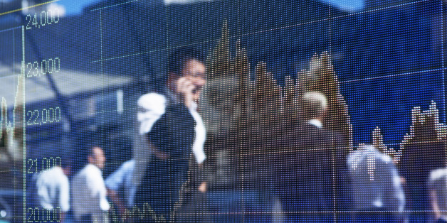 A silhouette of business man  talking on smart phone and walking on the road is reflected on the display of the stock price chart in the business district.