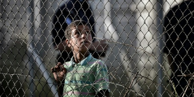 Un enfant regarde à travers les grillages du centre de détention de migrants de Moria à Mytilène en Grèce le 15 avril 2016