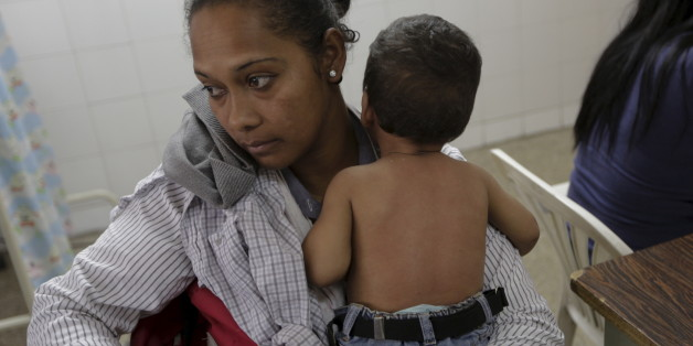 A woman who suspects her child to be infected with Zika virus, holds him as they wait at the emergency room in a hospital at the Petare slum in Caracas, Venezuela February 4, 2016. REUTERS/Marco Bello