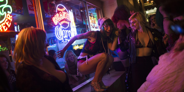 An exotic dancer performs outside a bar window on Columbus Avenue during a funeral procession to symbolize the closure of Lusty Lady strip club in San Francisco, California September 1, 2013. United States' first and only unionized, employee-owned strip club shuts its doors on September 2 after its landlord refused to negotiate on a lower rent, local media reported Picture taken September 1, 2013. REUTERS/Stephen Lam (UNITED STATES - Tags: BUSINESS SOCIETY)