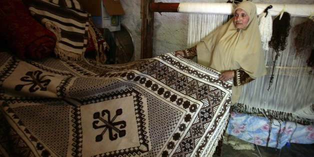 Nacera Benchenouf, 45, displays a carpet she made at her house in Babar village in the eastern city of Khenchela May 19, 2009. Babar carpets, which takes up to 3 months to make, are the most expensive carpets in Algeria. The patterns on these carpets represent the identity of the Shawia culture. To preserve this traditional tapestry craft, a museum for showcasing these carpets will soon be built at Babar village. REUTERS/Zohra Bensemra (ALGERIA SOCIETY)