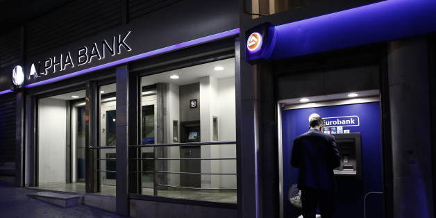 A customer uses an automated teller machines (ATM) operated by Eurobank Ergasias SA beside an Alpha Bank AE bank branch in Athens, Greece, on Tuesday, Nov. 3, 2015. Greece's four biggest banks may need as little as 1.2 billion euros ($1.3 billion) of new private funds to meet their expected contributions toward filling a capital shortfall, if they succeed in raising 3.2 billion euros through debt swaps. Photographer: Kostas Tsironis/Bloomberg via Getty Images