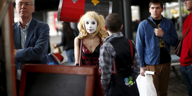 "A Paris Comic Con attendee waits as ""Harley Quinn"" during the first day of the event in Paris, France, October 23, 2015. The event draws thousands of costumed fans, panels of pop culture luminaries and features a sprawling floor of vendors at the Grande halle de la Villette in Paris. REUTERS/Benoit Tessier"