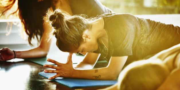 Woman resting between poses in yoga class in studio