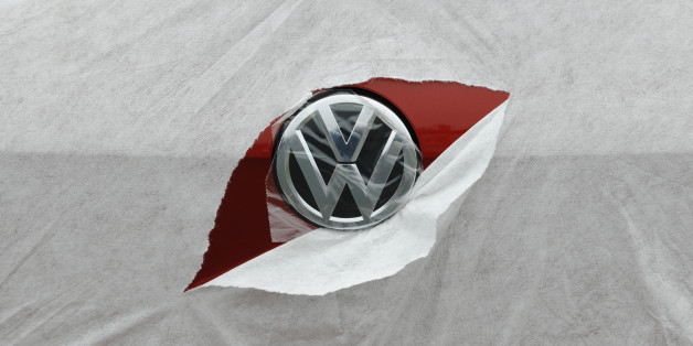 A VW badge is seen through torn wrapping as a Volkswagen Golf is delivered to a car dealership in Portslade near Brighton in southern England April 24, 2013. In the 12 months ending in March, car registrations in Britain rose 7.2 percent compared with the same period a year earlier. REUTERS/Luke MacGregor  (BRITAIN - Tags: TRANSPORT BUSINESS)