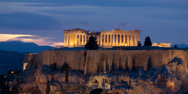 View onto the illuminated Parthenon temple on the Akropolis of Athens at dusk. The Dionysos theatre is seen at the lower left.