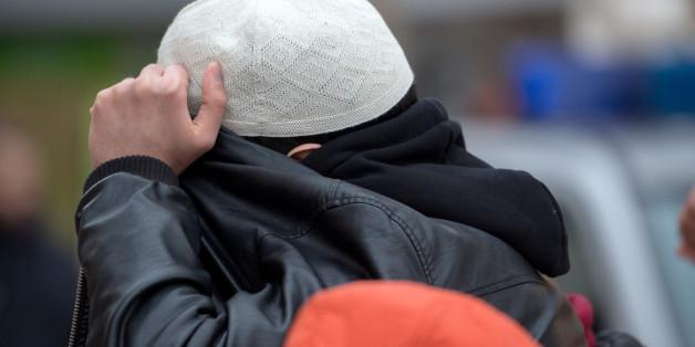 """Archivbild: Mit seiner Jacke verdeckt ein Mann aus dem Umfeld der Koran-Verteilaktion """"Lies"""" sein Gesicht"""