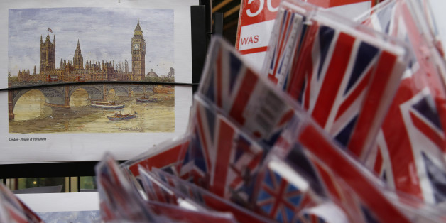 A poster of the houses of Parliament is displayed alongside Union flag souvenirs for sale in London, Britain, Thursday  December 17, 2015.  European Union leaders could clinch a deal with British Prime Minister David Cameron in February to prevent the bloc's second largest economy leaving, European Council President Donald Tusk said on Thursday. Cameron is seeking to renegotiate Britain's relationship with the bloc it joined in 1973 ahead of a referendum on membership to be held by the end of 20