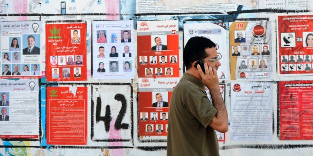 A Tunisian speaks on the phone as he walks past election posters put up on a street ahead of the parliamentary election in the Tunis suburb of Ariana on October 21, 2014. Tunisians vote on October 26, 2014 to elect their first parliament since the country's 2011 revolution, in a rare glimmer of hope for a region torn apart by post-Arab Spring violence and repression.  AFP PHOTO / FETHI BELAID        (Photo credit should read FETHI BELAID/AFP/Getty Images)