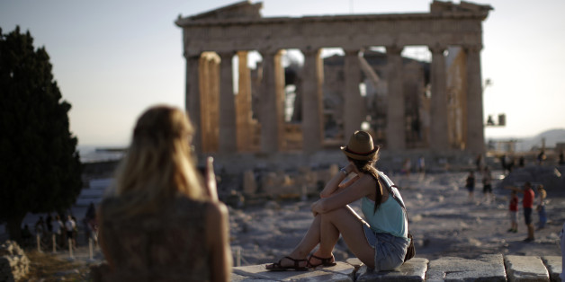 Tourists observe the Parthenon temple ruins on Acropolis Hill at sunset in Athens, Greece, on Monday, July 20, 2015. German Chancellor Angela Merkel held out the prospect of limited debt relief as crisis-ravaged Greece prepares to reopen its banks three weeks after they were shut. Photographer: Matthew Lloyd/Bloomberg via Getty Images