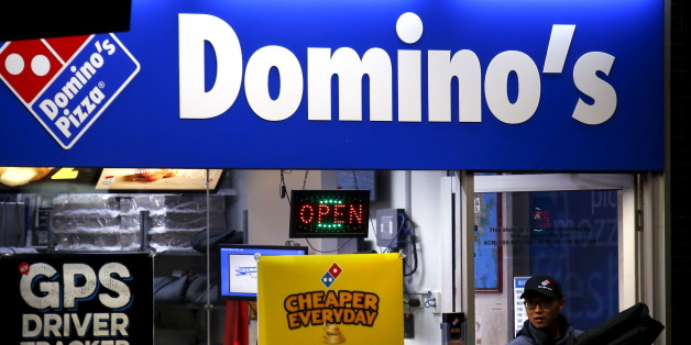 A worker carries a pizza for delivery as he exits a Domino's pizza store in Sydney, Australia, August 12, 2015. Fast food may be falling out of favour in many countries around the world but companies are making healthy profits and boldly innovating in the unlikely market of Australia. Contrary to stereotypes of a beach-going community of fitness fanatics, official data out this week showed 40 percent of Australian adults are dangerously obese and have a poor diet that includes lashings of fast f