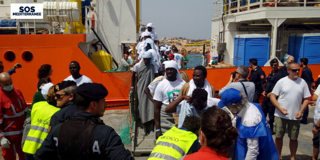 Migrants disembark from the SOS Mediterranee ship Aquarius at the Italian island of Lampedusa in this April 18, 2016.