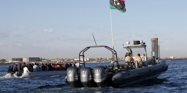 Libyan coast guards (R) escort migrants, who tried to flee to Europe, after the migrants were stopped by the coast guards and made to head to Tripoli September 29, 2015. The North African country has turned into a major hub for human traffickers smuggling African migrants by boat to Italy, with the Libyan coastguard under pressure from Europe to stem the flow. REUTERS/Ismail Zitouny
