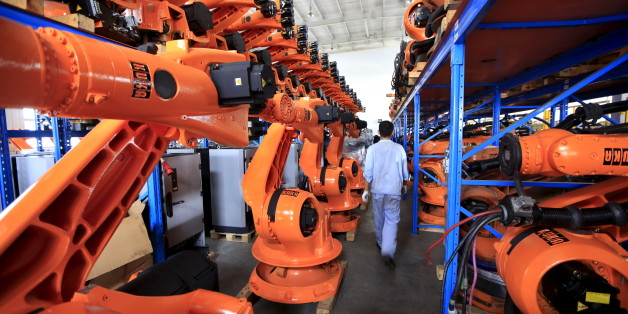 A worker walks past second-hand robots in a factory in Shanghai, August 21, 2015. More than a hundred second-hand robots used to make Audi A3s at a German car factory are going through refurbishment at a Wecan Group factory in Shanghai. Picture taken August 21, 2015. REUTERS/Aly Song