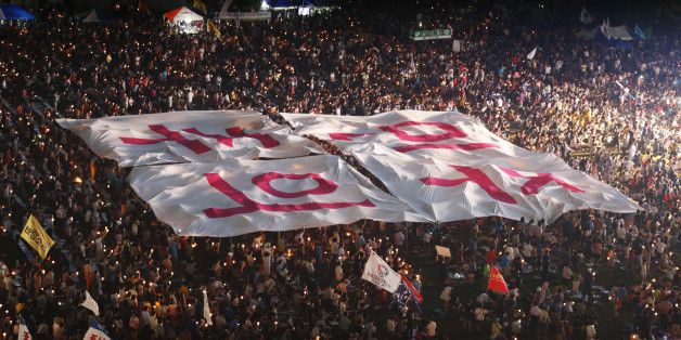 "People hold a large banner, which reads,""Democracy"", during a candle-light demonstration demanding an apology from South Korean President Park Geun-Hye to the nation, and calling for the resignation of National Intelligence Service (NIS) chief Nam Jae-joon in central Seoul August 10, 2013. According to local media reports, the spy agency's former chief Won Sei-hoon, who served under the regime of former President Lee Myung-Bak, was indicted on June 14, 2013 on charges of interfering in last Dece"