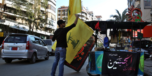 In this Feb. 29, 2016 photo, a vendor sells Hezbollah and religious flags and other memorabilia , in the southern suburbs of Beirut, Lebanon. Lebanon's central bank governor said Monday, April 18, 2016 that Beirut will abide by a U.S. law that imposes sanctions on banks that knowingly do business with the militant Hezbollah group. (AP Photo/Bilal Hussein)