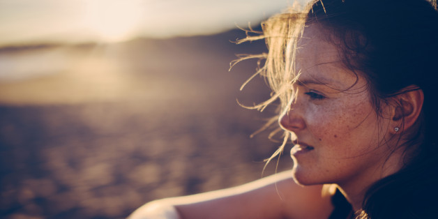Portrait of a blond haired woman with smartwatch at the beach after running.