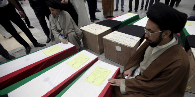 Clerics pray next to coffins of victims of Friday's bombing at the Imam Sadeq mosque in Kuwait City, at the international airport in Najaf, south of Baghdad, June 27, 2015. The attack, which killed 27 and injured more than 200 at the mosque, was claimed by Islamic State's Wilayat of Najd division. Some of victims' bodies have been brought to the Shi'ite holy cities of Najaf and Karbala in Iraq for burial. The coffins are seen shrouded with Kuwaiti flags. REUTERS/Alaa Al-Marjani
