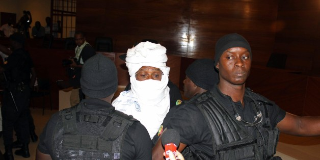 CORRECTS NAME OF PHOTOGRAPHER  Security personnel surround former Chadian dictator Hissene Habre inside the court in Dakar, Senegal, Monday, July 20, 2015. The trial of former Chadian dictator Hissene Habre, accused of overseeing the deaths of thousands, had a chaotic beginning Monday as security forces ushered the ex-leader into and then out of the Senegal courtroom amid protests by his supporters.(AP Photo/Ibrahima Ndiaye)