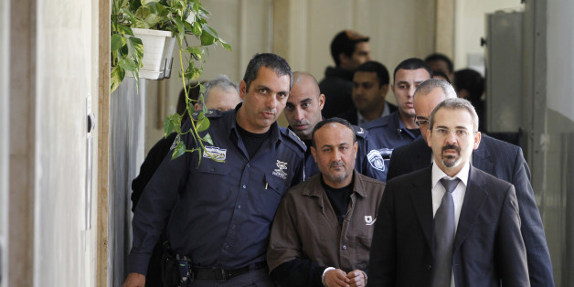 An Israeli prison guard (L) escorts jailed Fatah leader Marwan Barghouti (C) to a deliberation at Jerusalem Magistrate's court January 25, 2012. Convicted of murder for his role in attacks on Israelis, Barghouti was jailed for life by Israel in 2004. 