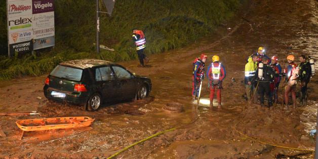 Feuerwehrmänner und Rettungstaucher stehen um den Gullischacht, in dem zwei Menschen starben