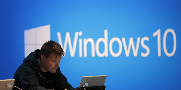 A man works on a laptop computer near a Windows 10 display at Microsoft Build in San Francisco, California April 29, 2015. REUTERS/Robert Galbraith