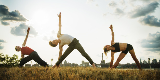 Young fit people doing yoga in the East River Park in Williamsburg, Brooklyn, New York City