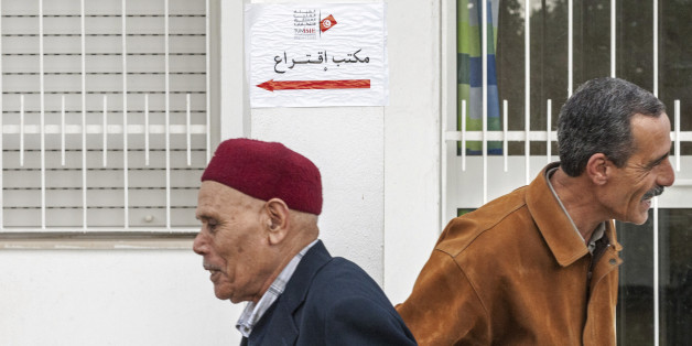 Tunisians walk past a polling station in Tunis, Tunisia, Sunday Dec. 21 , 2014. Tunisians voted on Sunday for a new president in a runoff between a symbol of the country's previous regimes and a veteran human rights activist who came to power after the revolution of 2011. (AP Photo/Ilyess Osmane)