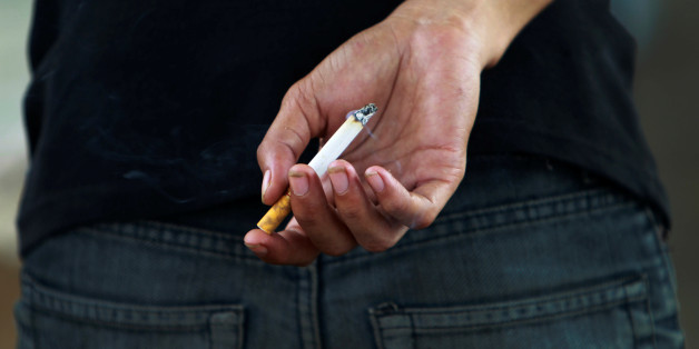 An Indonesian youth holds a cigarette while waiting for a train in Jakarta May 24, 2012.  REUTERS/Beawiharta/File Photo
